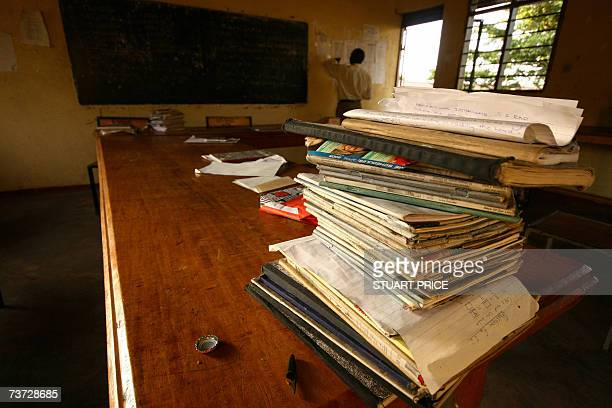 A pile of books sit on a table in a classroom at St Denis' Secondary School in Ggaba a suburb of the capital Kampala as a teacher checks a pupil list...