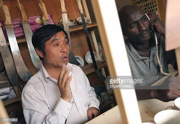 UGANDA Kampala Martin Meng a hardware trader from China discusses with a customer through the bars of his shop 03 November 2006 in the downtown area...