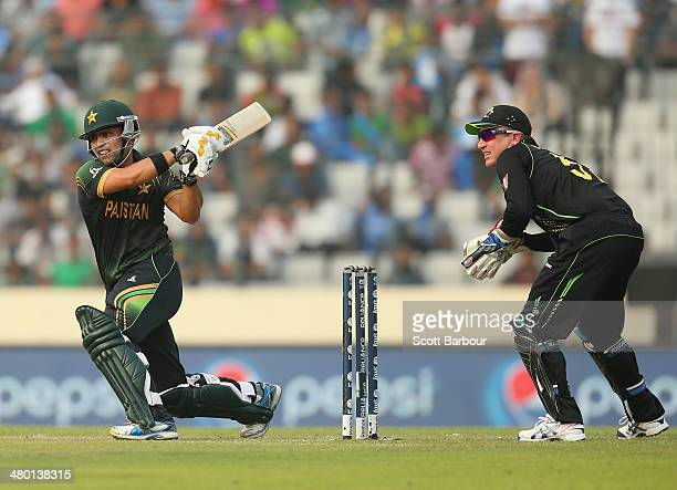 Kamran Akmal of Pakistan hits a boundary as Brad Haddin of Australia looks on during the ICC World Twenty20 Bangladesh 2014 match between Australia...