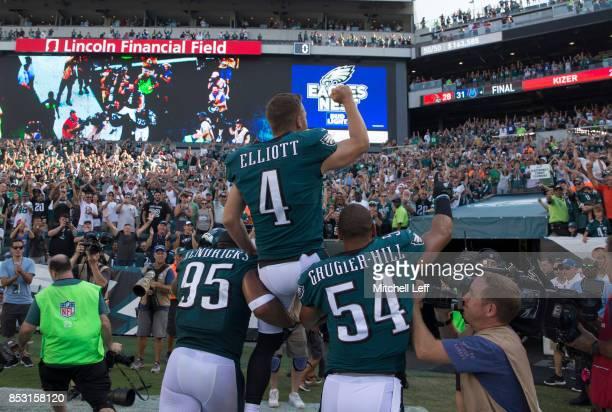 Kamu GrugierHill and Mychal Kendricks of the Philadelphia Eagles carry Jake Elliott of the Philadelphia Eagles off the field after the game against...