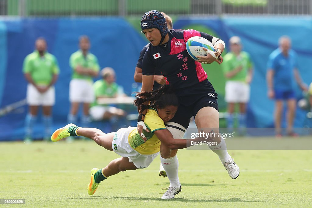 Kana Mitsugi of Japan carries the ball under pressure from Edna Santini of Brazil during the Women's Pool C rugby match on Day 2 of the Rio 2016...