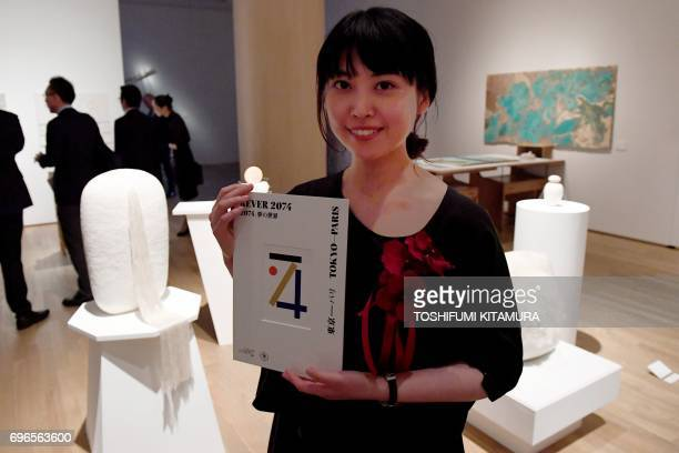 Kanako Kitabayashi one of three winners of the 'Rever 2074' art competition poses in front of her creation 'Peau' after the awards ceremony in Tokyo...