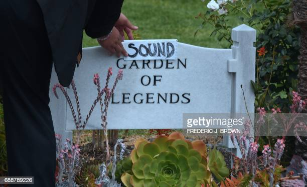 Kanan Sanchez places a folded sheet of paper with the word 'Sound' over the stone at the Garden of Legends section of the Hollywood Forever Cemetery...