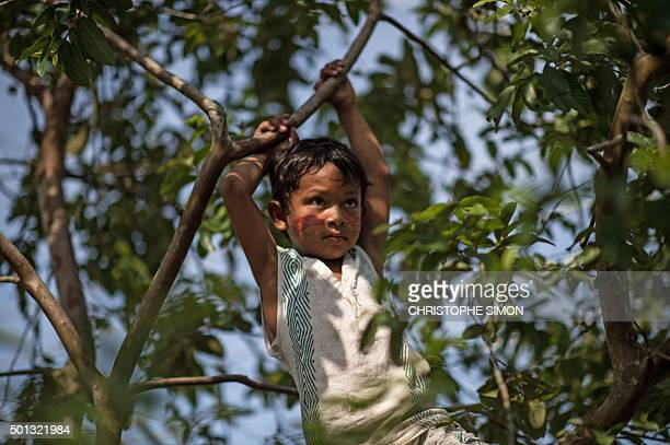 A Kanbeba indigenous boy plays in Tres Bocas village on the bank of the Rio Negro in the Amazonia Brazil on December 9 2015 AFP PHOTO / Christophe...
