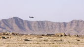 A helicopter flies past as British soldiers from 2 Squadron Royal Air Force Regiment conduct a patrol outside Kandahar Air Field 04 November 2006 The...