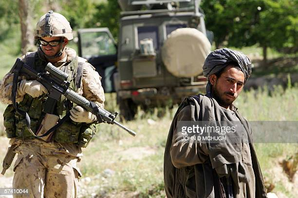 A member of 1st Princess Patricia's Canadian Light Infantry stands guard over a local man during a village search in northern Kandahar 24 April 2006...