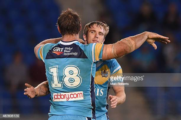 Kane Elgey of the Titans celebrates victory with Dave Taylor during the round 21 NRL match between the Gold Coast Titans and the Parramatta Eels at...