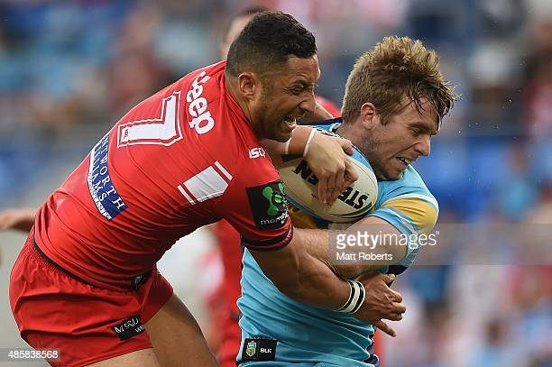Kane Elgey of the Titans is tackled by Benji Marshall of the Dragons the round 25 NRL match between the Gold Coast Titans and the St George Illawarra...