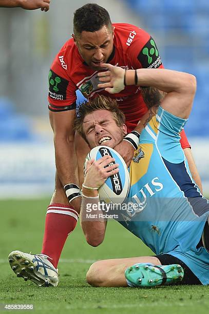 Kane Elgey of the Titans is tackled by Benji Marshall of the Dragons during the round 25 NRL match between the Gold Coast Titans and the St George...