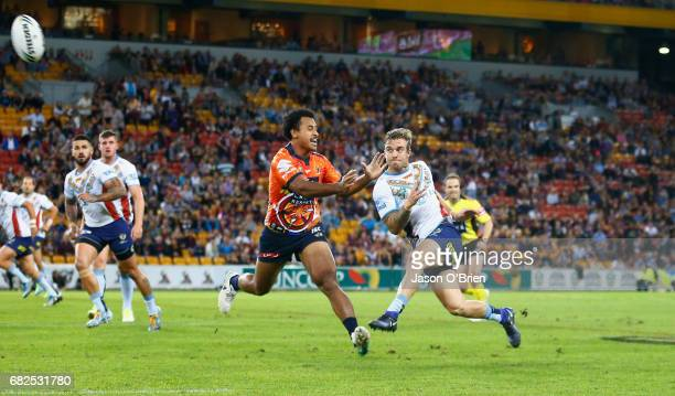 Kane Elgey of the titans kicks downfield during the round 10 NRL match between the Melbourne Storm and the Gold Coast Titans at Suncorp Stadium on...