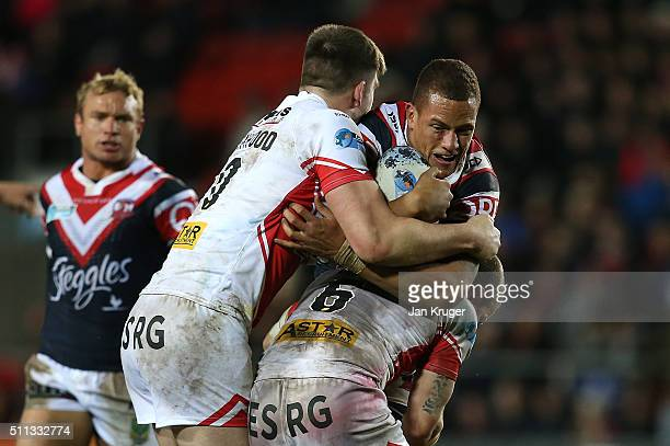 Kane Evans of Sydney Roosters is held up by James Roby Travis Burns and Luke Thompson of St Helens during the World Club Series match between St...