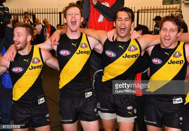 Kane Lambert Jack Riewoldt Alex Rance and Reece Conca of the Tigers sing the song in the rooms after winning the round five AFL match between the...