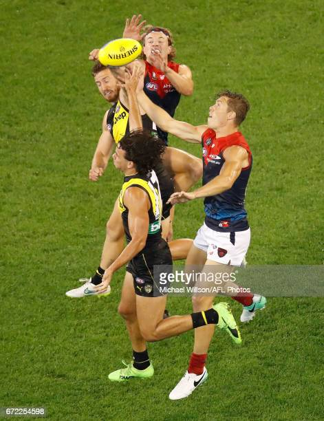 Kane Lambert of the Tigers Daniel Rioli of the Tigers Jayden Hunt of the Demons and Jake Melksham of the Demons compete for the ball during the 2017...
