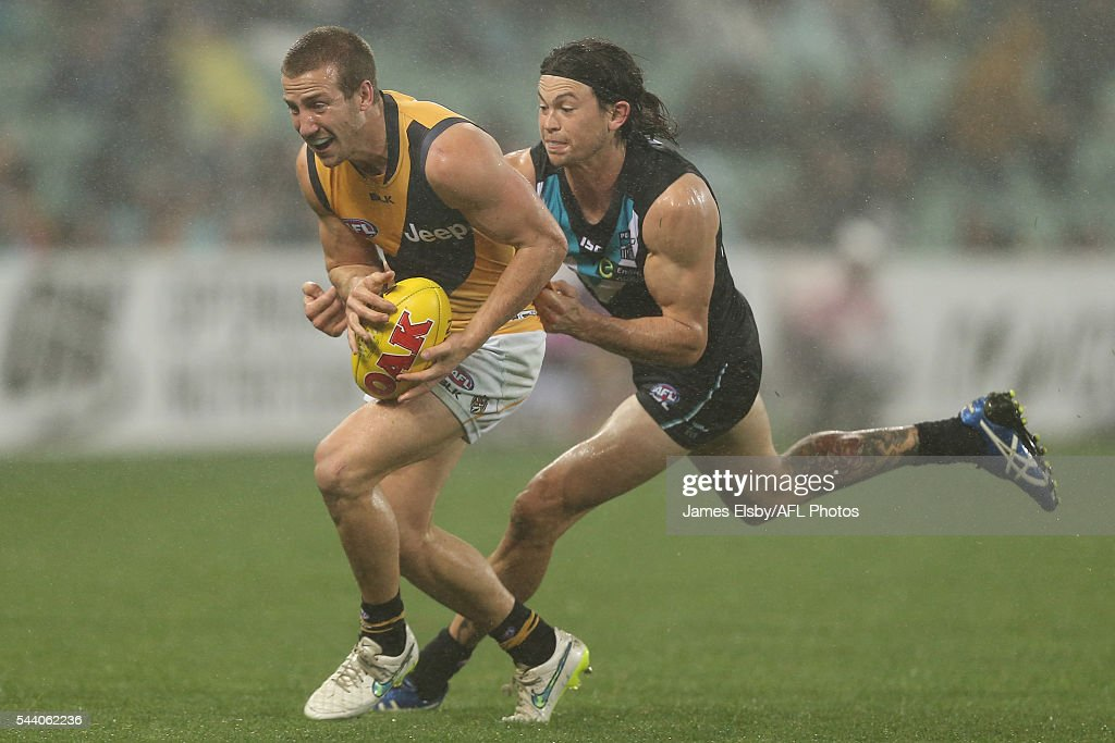 Kane Lambert of the Tigers is tackled by Jasper Pittard of the Power during the 2016 AFL Round 15 match between Port Adelaide Power and the Richmond Tigers at Adelaide Oval on July 1, 2016 in Adelaide, Australia.