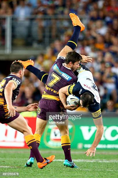 Kane Linnett of the Cowboys is spear tackled by Ben Hunt of the Broncos during the 2015 NRL Grand Final match between the Brisbane Broncos and the...