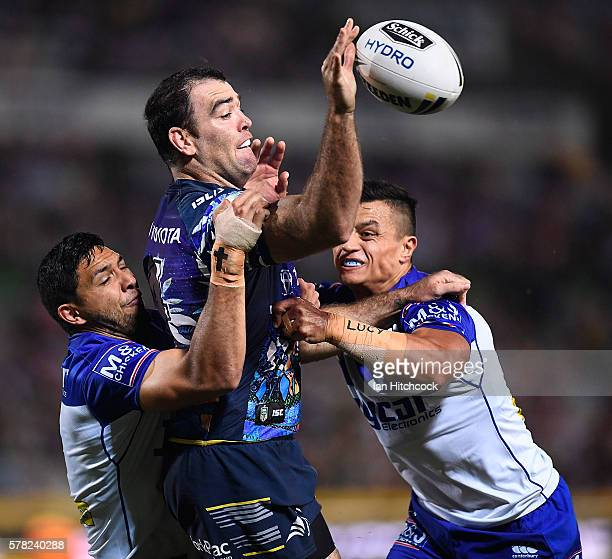 Kane Linnett of the Cowboys passes the ball despite the tackle of Curtis Rona and Sam Perrett of the Bulldogs during the round 20 NRL match between...