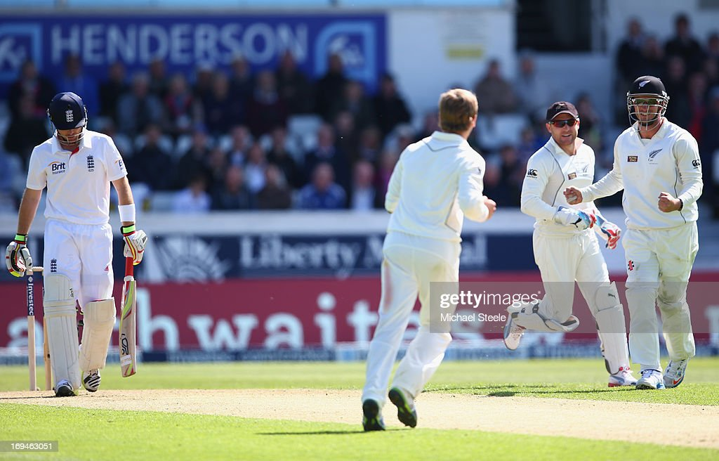 Kane Williamson celebrates with Brendon McCullum and Hamish Rutherford of New Zealand after taking the wicket of Ian Bell of England during day two...