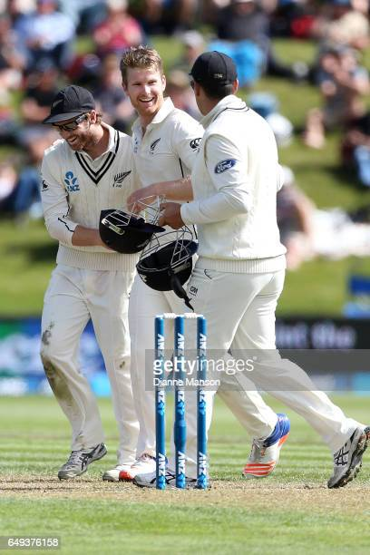 Kane Williamson Jimmy Neesham and Ross Taylor of New Zealand celebrate the dismissal of Faf du Plessis of South Africa during day one of the First...