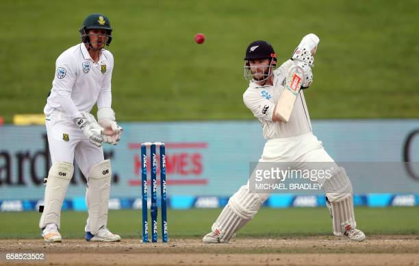 Kane Williamson of New Zealand plays a shot as Quinton de Kock of South Africa looks on during day four of the third Test cricket match between New...
