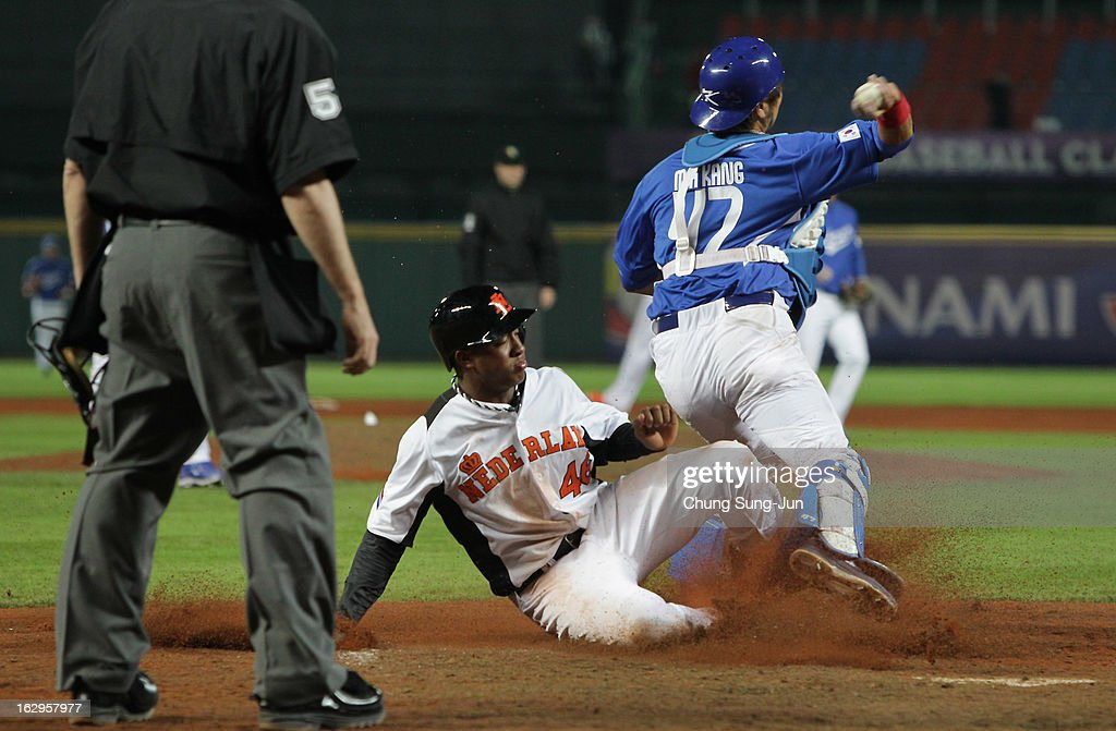 Kang Min-Ho of South Korea tags out Jonathan Schoop of Netherlands as he slides into home base in the seventh inning during the World Baseball Classic First Round Group B match between South Korea and the Netherland at Intercontinental Baseball Stadium on March 2, 2013 in Taichung, Taiwan.
