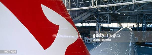 A kangaroo logo on a jet airliner parked in a hangar for repairs.
