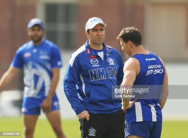 Kangaroos coach Brad Scott talks with Brent Harvey as Daniel Wells looks on during a North Melbourne Kangaroos AFL training session at Arden Street...