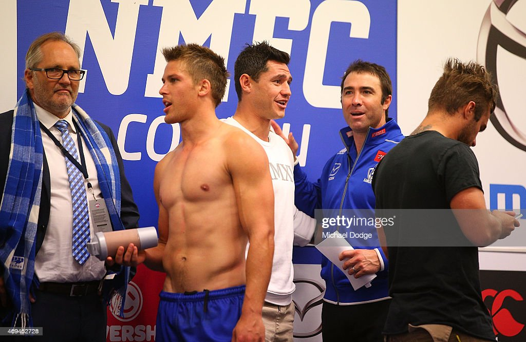 Kangaroos head coach Brad Scott catches up with former player Aaron Edwards after the win during the round two AFL match between the North Melbourne...