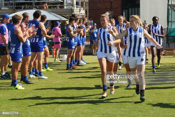 Kangaroos players cpa on their women's team after the JLT Community Series AFL match between the North Melbourne Kangaroos and the Hawthorn Hawks at...
