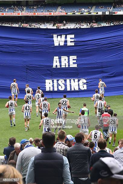 Kangaroos players run to their banner during the round five AFL match between the Collingwood Magpies and the North Melbourne Kangaroos at Melbourne...