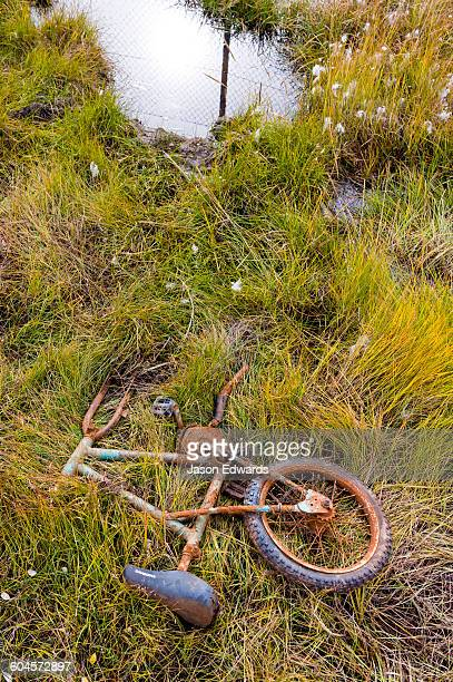 A broken childrens bike rusting in ditch beside an airfield in an arctic village.