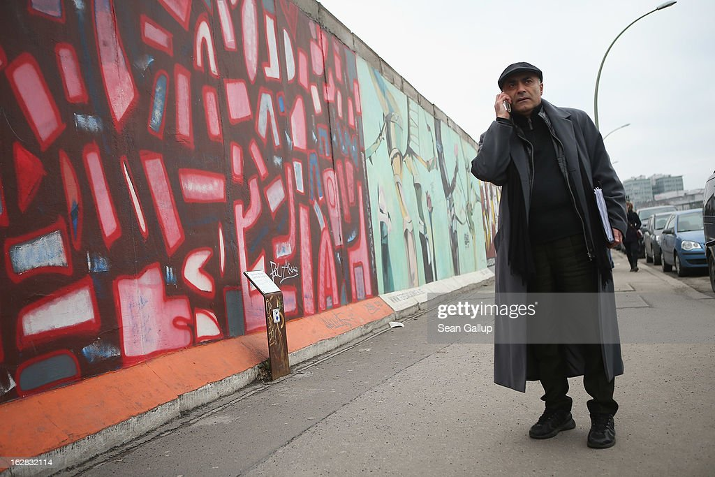 Kani Alavi, Chairman of the East Side Gallery Artists' Association, talks on a phone while standing next to the East Side Gallery, which is the longest still-standing portion of the former Berlin Wall, close to where a new hotel is scheduled to be built on February 28, 2013 in Berlin, Germany. According to media reports the developer in charge of the project plans to remove an approximately 25-meter long piece of the Wall and transfer it elsewhere in order to allow access to the construction site. Critics, including East Side Gallery mural artists and Spree River embankment development opponents, decry the move, citing the East Side Gallery's status as a protected landmark and a majortourist attraction.