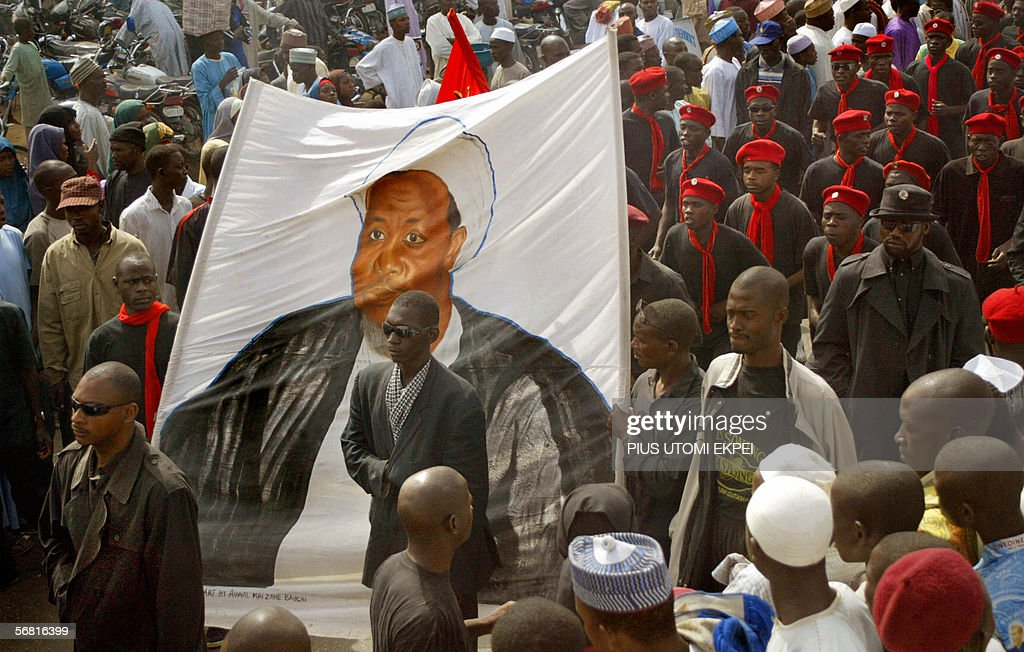 Blackshirted followers of a hardline Shiite Muslim sect carry a banner depicting Ibrahim Zakzaky a Nigerian Shiite radical who wants to set up an...