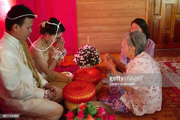 Kanokporn and Montri Thi are given respect by relatives during ceremonies at their wedding in Ta Par Mok Thailand Thai Buddhist marriage ceremonies...