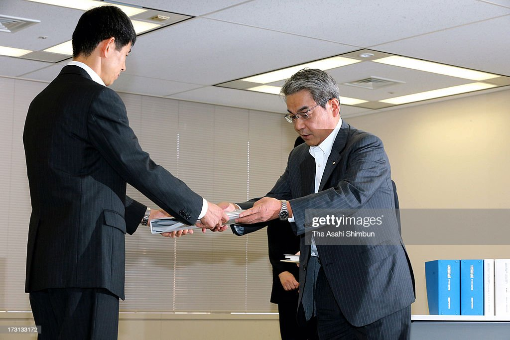 Kansai Electric Power Co director Ikuo Morinaka (R) hands in an application to the Nuclear Regulation Authority officer on July 8, 2013 in Tokyo, Japan. Four utilities of Hokkaido, Kansai, Shikoku and Kyushu apply for the safety examinations of ten reactors of five nuclear power plants, on the day tougher standards took effect to prevent a recurrence of the 2011 Fukushima nuclear crisis.