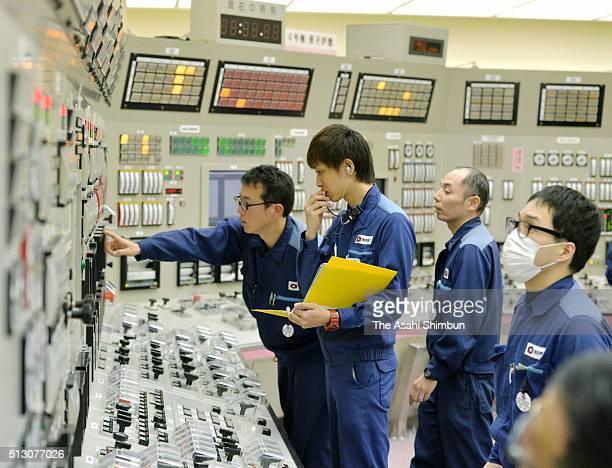 Kansai Electric Power staffs check the metres and instruments after the shut down of the No 4 reactor at the centra control room of the Takahama...