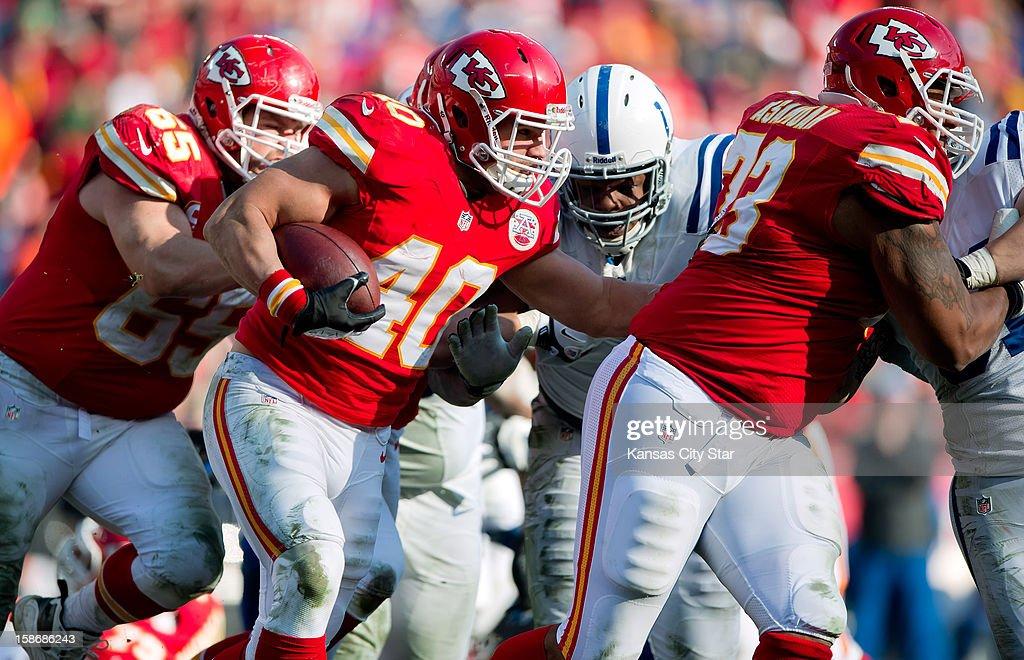 Kansas City Chiefs running back Peyton Hillis runs past Indianapolis Colts defensive end Ricardo Mathews in the second quarter at Arrowhead Stadium...