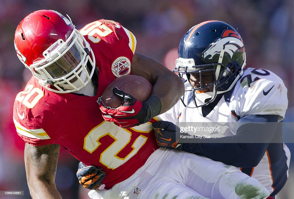 Kansas City Chiefs running back Shaun Draughn (20) picks up six yards before being stopped by Denver Broncos strong safety Mike Adams (20) in the first quarter at Arrowhead Stadium on Sunday, November 25, 2012, in Kansas City, Missouri. The Denver Broncos defeated the Kansas City Chiefs, 17-9.