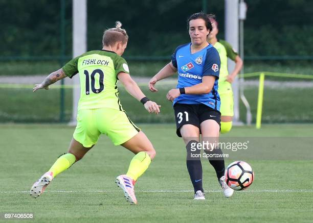 Kansas City defender Christina Gibbons sends the ball past Seattle Reign FC midfielder Jessica Fishlock in the first half of an NWSL match between...