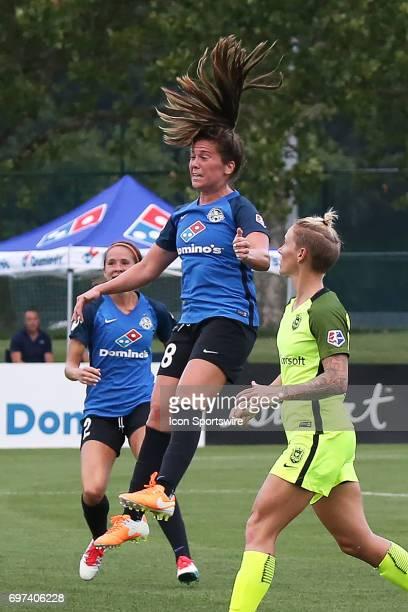 Kansas City midfielder Alexa Newfield sends the header over Seattle Reign FC goalkeeper Haley Kopmeyer for a goal in the first half of an NWSL match...