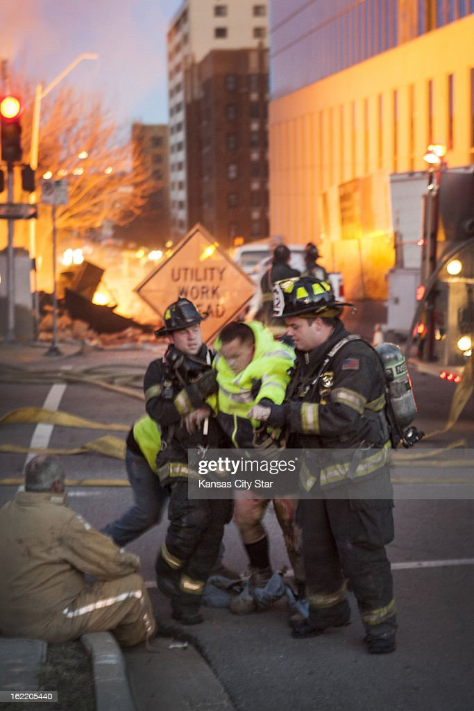 Kansas City, Mo., firefighters help a dazed victim at the scene of an explosion and 4-alarm fire at JJ's restaurant on The Country Club Plaza, in Kansas, City, Tuesday, February 19, 2013.