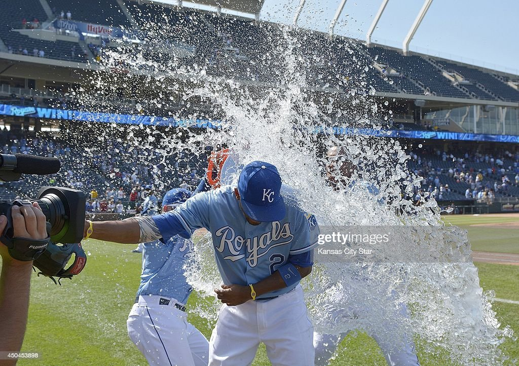 Kansas City Royals' Alcides Escobar gets doused during a post game interview by Salvador Perez and Kelvin Herrera after the teams 4-1 win over the Cleveland Indians during Wednesday's baseball game on June 11, 2014 at Kauffman Stadium in Kansas City, Mo.
