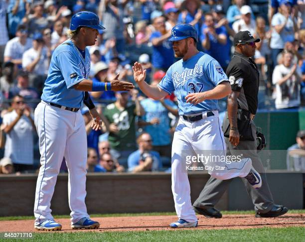Kansas City Royals' Brandon Moss and Salvador Perez greet each other after both scored on a single by Alcides Escobar in the second inning against...