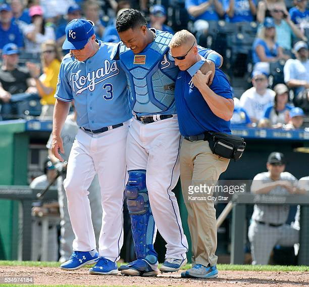 Kansas City Royals catcher Salvador Perez is helped off the field after he and third baseman Cheslor Cuthbert collided chasing a foul ball in the...