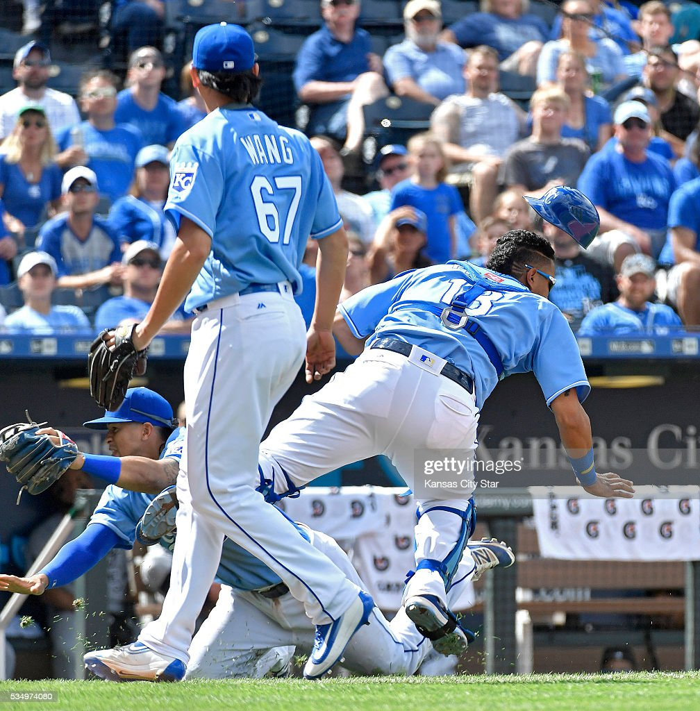 Kansas City Royals catcher Salvador Perez, right, and third baseman Cheslor Cuthbert collide in front of relief pitcher Chien-Ming Wang (67) while chasing a foul ball in the ninth inning against the Chicago White Sox on Saturday, May 28, 2016, at Kauffman Stadium in Kansas City, Mo. Perez had to be helped off the field.