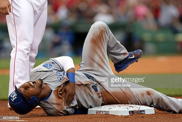 Kansas City Royals center fielder Jarrod Dyson writhes in pain after hitting his shoulder while diving unsuccessfully back to first base The Boston...