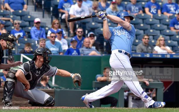 Kansas City Royals designated hitter Brandon Moss follows through on a grand slam in the first inning in front of Chicago White Sox catcher Rob...