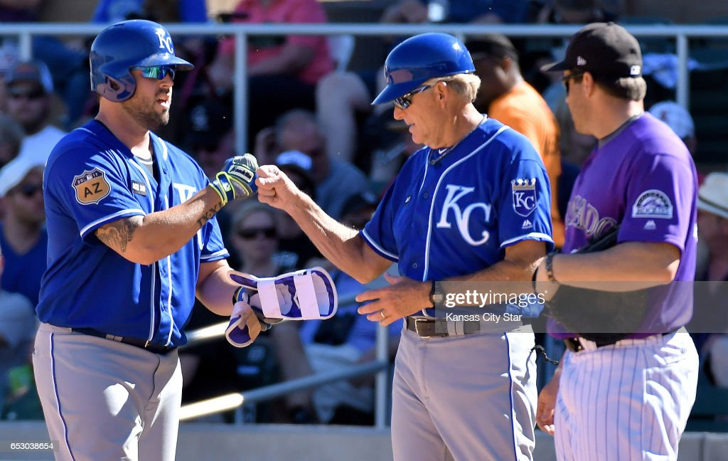 Kansas City Royals' Mike Moustakas is greeted by first base coach Rusty Kuntz after reaching first on a groundout of Raul Mondesi at second in the sixth inning during a spring training baseball game on Monday, March 13, 2017 in Scottsdale, Ariz.