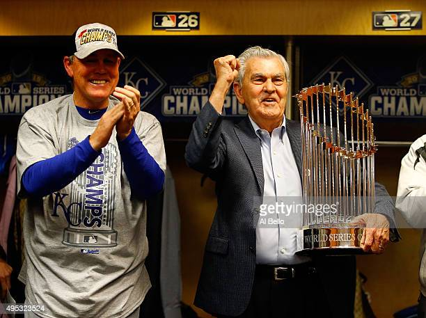 Kansas City Royals owner David D Glass right holds the Commissioner's Trophy as manager Ned Yost of the Kansas City Royals reacts after the Kansas...