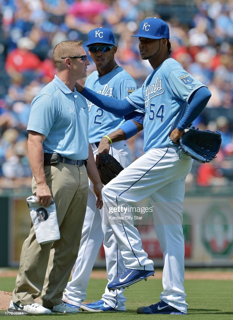 Kansas City Royals starting pitcher Ervin Santana (54) leans on head trainer Nick Kenney after taking a line drive off his leg in the third inning during Sunday's baseball game on August 25, 2013, at Kauffman Stadium in Kansas City, Missouri.