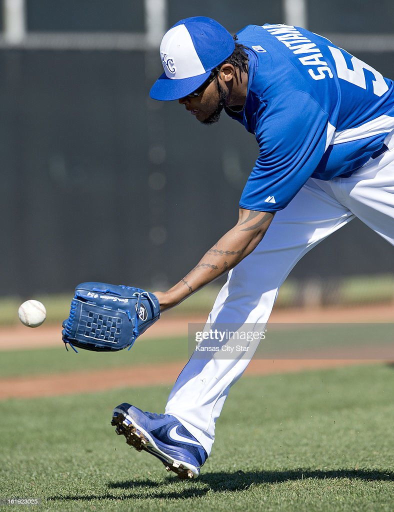 Kansas City Royals starting pitcher Ervin Santana (54) scoops the ball back to the catcher in bunts back to the pitcher drills at spring training in Surprise, Arizona, Sunday, February 17, 2013.
